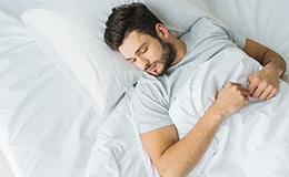 Man with brown hair resting in bed