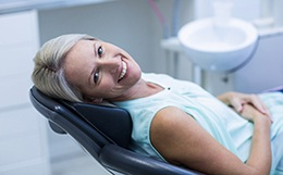 Blond female dental patient leaning back in chair and smiling